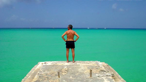 Photo of Paul Bardo in front of the open sea with his arms on his hips.